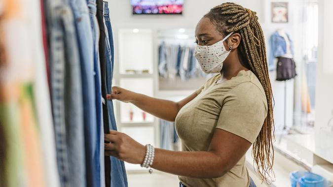 Covid-19: Woman customer choosing clothes at the mall store stock photo