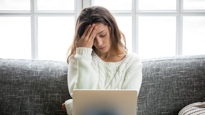 Frustrated woman worried about problem sitting on sofa with laptop stock photo