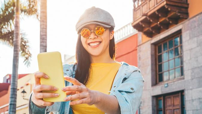 Happy Asian girl using mobile smartphone outdoor - Chinese social influencer having fun making video story for new trends social networks app - People, millennial generation and technology concept stock photo