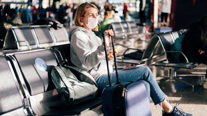 A female passenger in a medical mask is waiting for a flight at the airport. stock photo