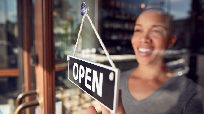 Female Owner Of Start Up Coffee Shop Or Restaurant Turning Round Open Sign On Door.