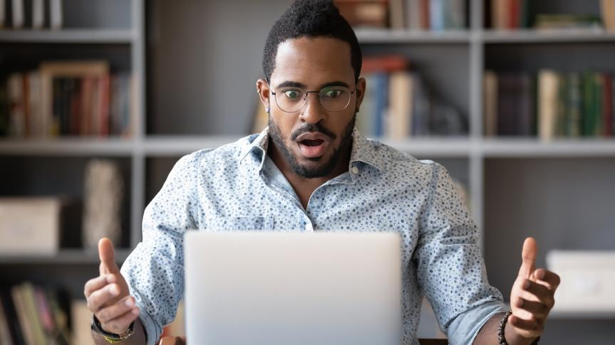 Front view shocked millennial african american man in glasses looking at laptop screen, received email with unbelievable news.