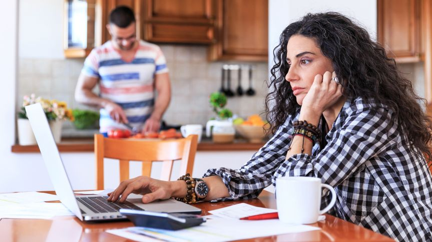 Young woman sitting at home and making home finances.