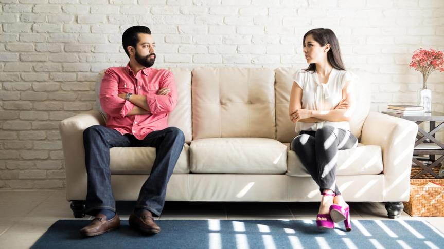 Husband and wife sitting on sofa with their arms crossed and looking at each other after a fight in living room.