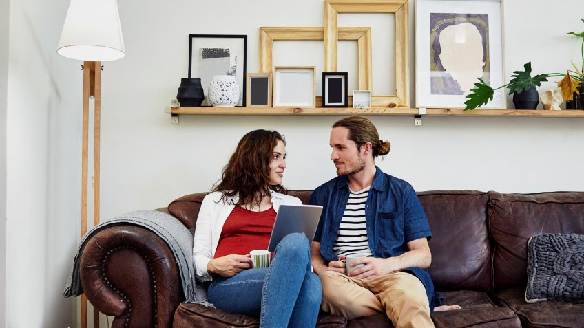 Shot of a young couple relaxing on the sofa with a digital tablet at home.