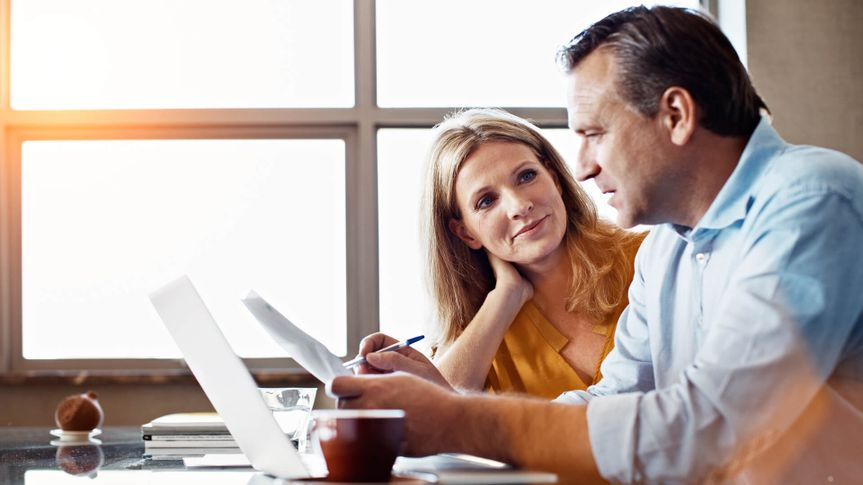 Shot of a mature couple sitting at their dining room table doing online banking using a laptop.