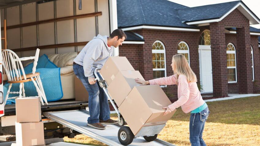 Mid adult couple (30s) unloading moving van.
