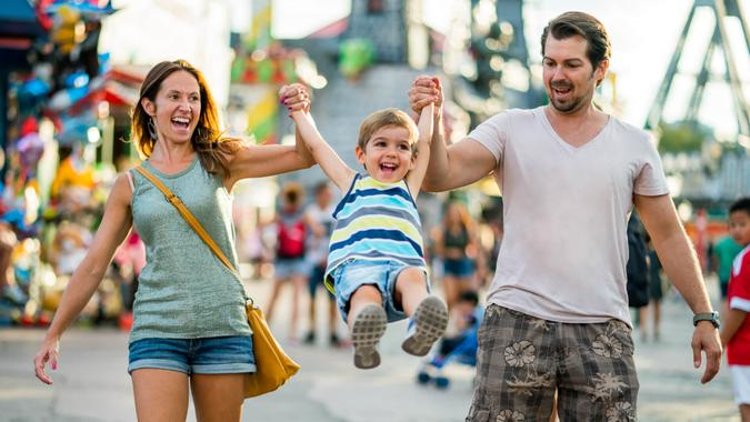 three years old boy with happy smiling mom and dad having fun on summer vacation day in themepark.
