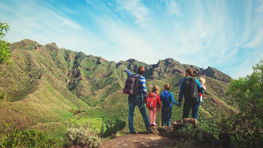 family with three kids hiking in mountains.