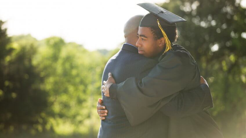 African American Father hugging his son graduation day.