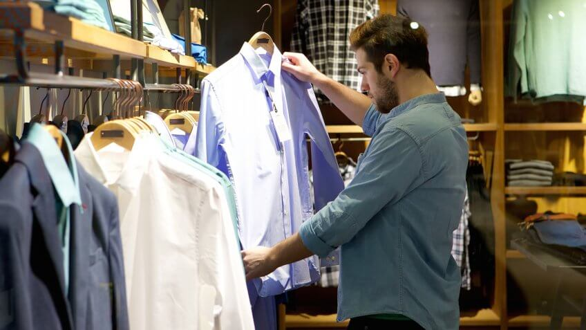 Portrait of a young man shopping for clothes at store.