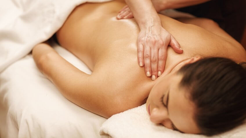 Young woman receiving back massage at spa salon.