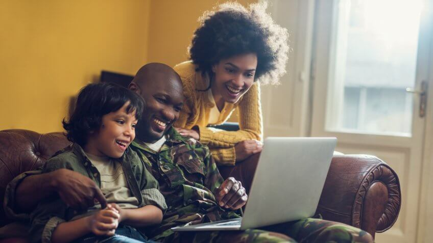Happy military family relaxing at home and using computer together.