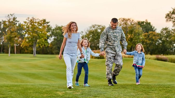 Happy family walking on the grass.