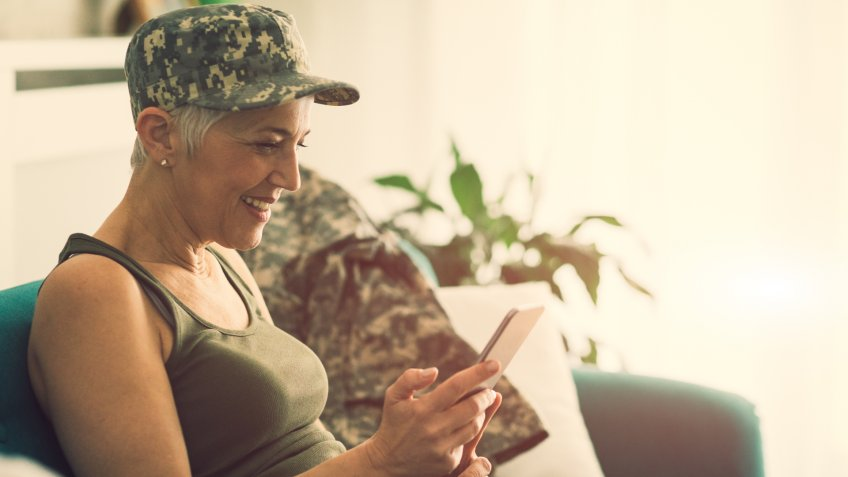 Military mature woman using smart phone at home.