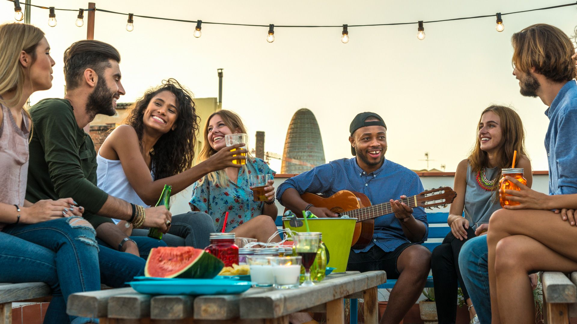 Young adults celebrating life and friendship on a rooftop in Barcelona, Spain.