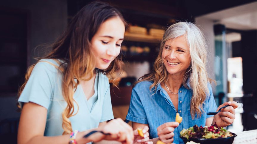 Beautiful grandmother and teenage granddaughter sitting at a restaurant eating a meal together.
