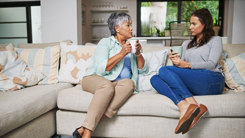 Shot of a young woman and her mother catching up on the sofa while drinking coffee.