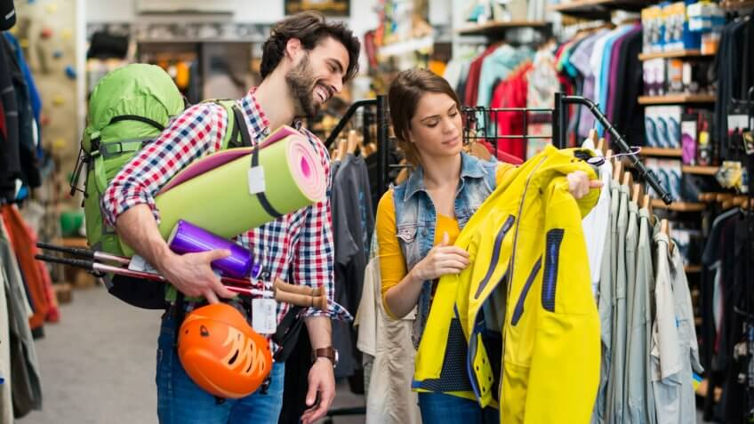 Man in sports store picking some hiking equipment, and asking a sales person about yellow jacket.