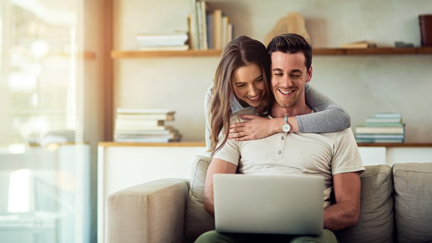 Shot of a young woman hugging her husband while he uses a laptop on the sofa at home.