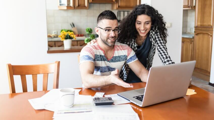 Couple working at home, using laptop.