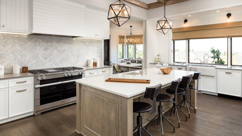 Kitchen Interior with Island, Sink, Cabinets, and Hardwood Floors in New Luxury Home.