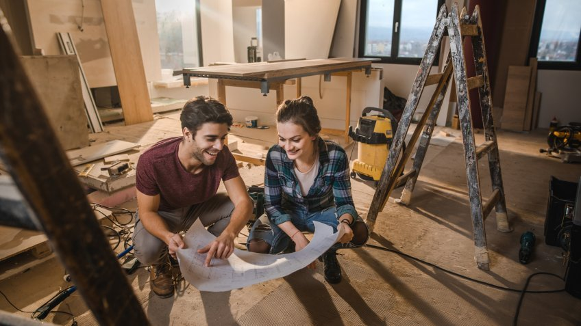 Young happy couple examining blueprints while being on construction site in their apartment.