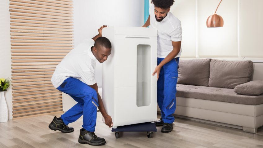 Two Young Male Movers Placing The White Cabinet On Wheel In The Living Room.