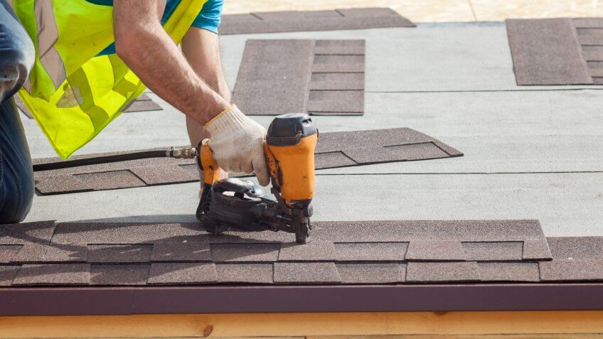 Construction worker putting the asphalt roofing shingles with nail gun on a new frame house