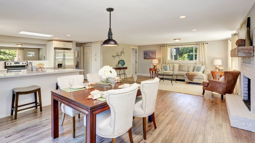 Open floor plan dining area with elegant table setting and white soft chairs