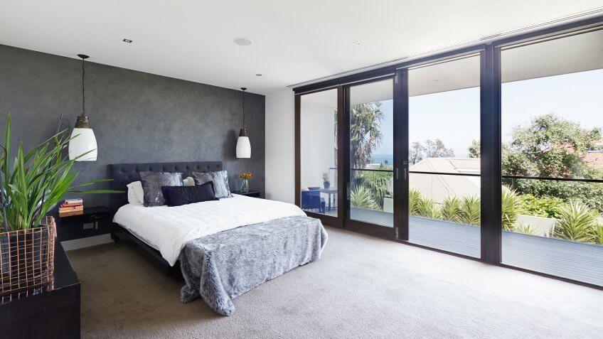 Spacious interior of designer master bedroom in luxury contemporary Australian home.
