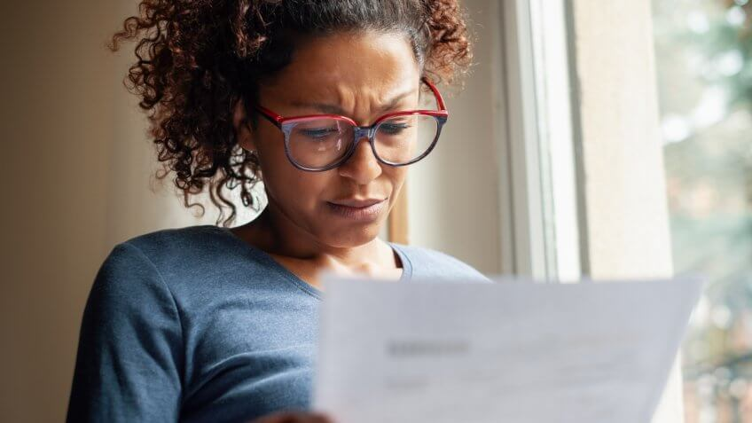 Portrait of worried black woman standing beside window.