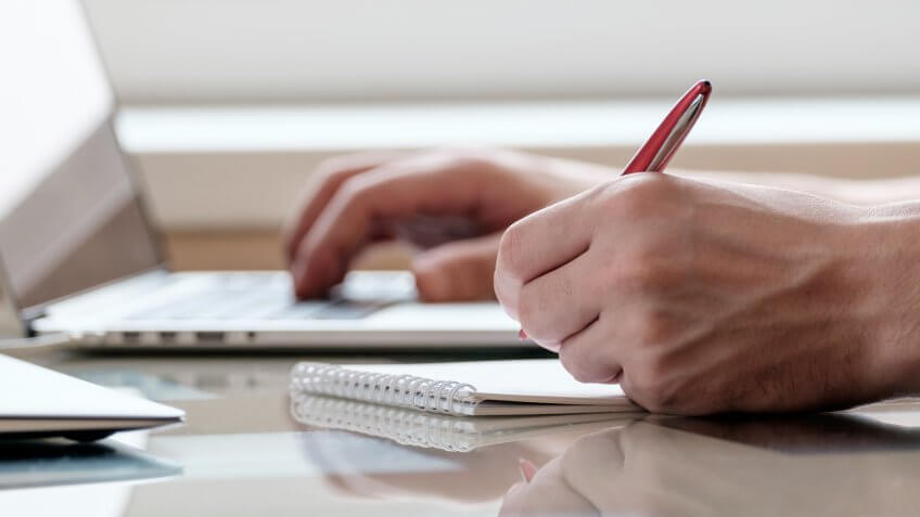 Close up of male hands with laptop computer, notebook and pen taking notes in business office.
