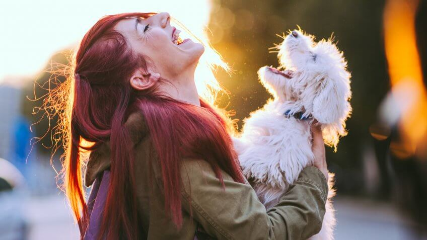 Attractive Redheaded Girl and White Puppy Smiling Together.