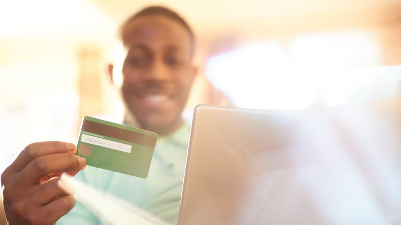 Young black male using digital tablet in the comfort of his home to do some online shopping.