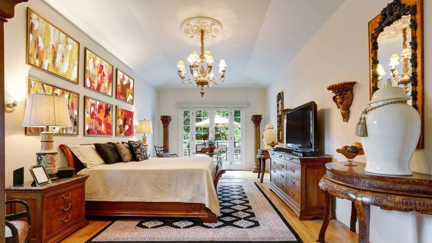 Luxury large master bedroom interior with antique carved wooden furniture, king size bed, vintage chandelier and hardwood floor.
