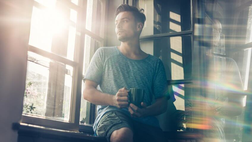 Low angle view of young thoughtful man looking through window during his coffee time at home.