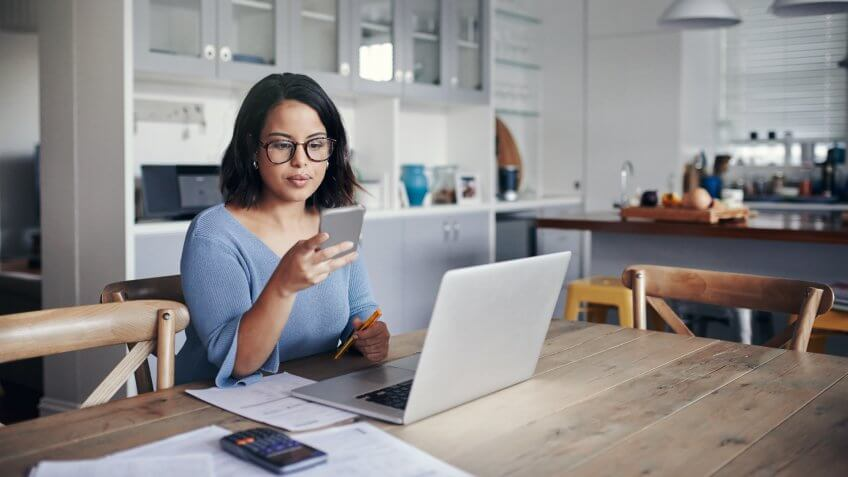 Shot of a young woman using a mobile phone and laptop while working from home.