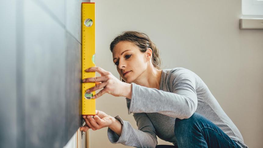 Woman wearing grey shirt using leveling tool at home.