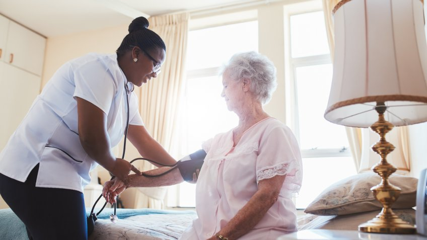 Female nurse doing blood pressure measurement of a senior woman patient.
