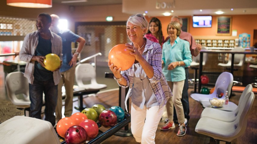 Group of seniors at a bowling alley, five senior friends can be seen in the background whilst a woman takes her turn.