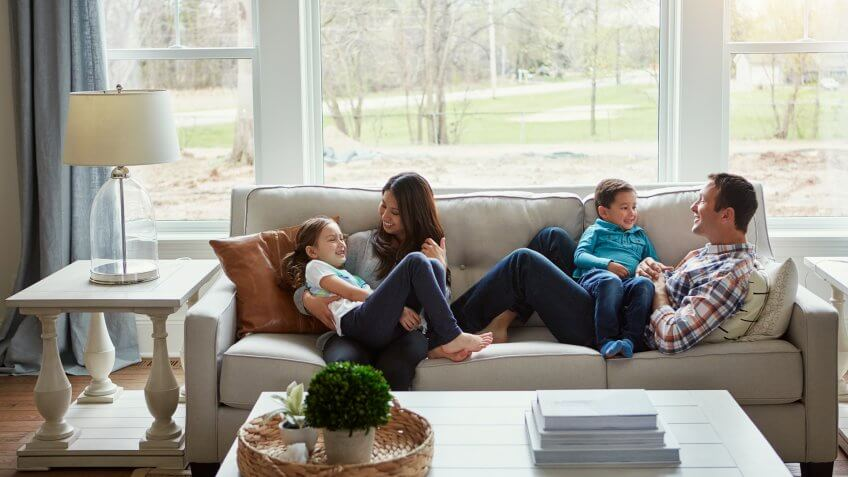 Shot of a happy young family of four relaxing together on the sofa at home.