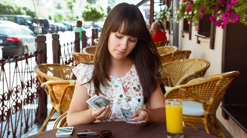 Sad woman in cafe counting money.