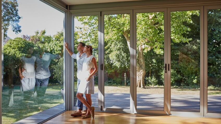 Full length of loving mid adult couple looking through glass window.