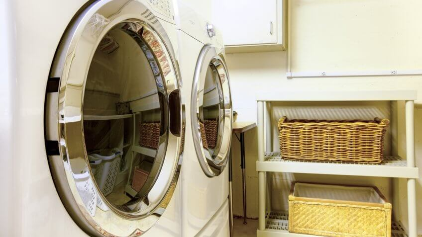 Old style laundry room with modern appliances and wicker baskets.