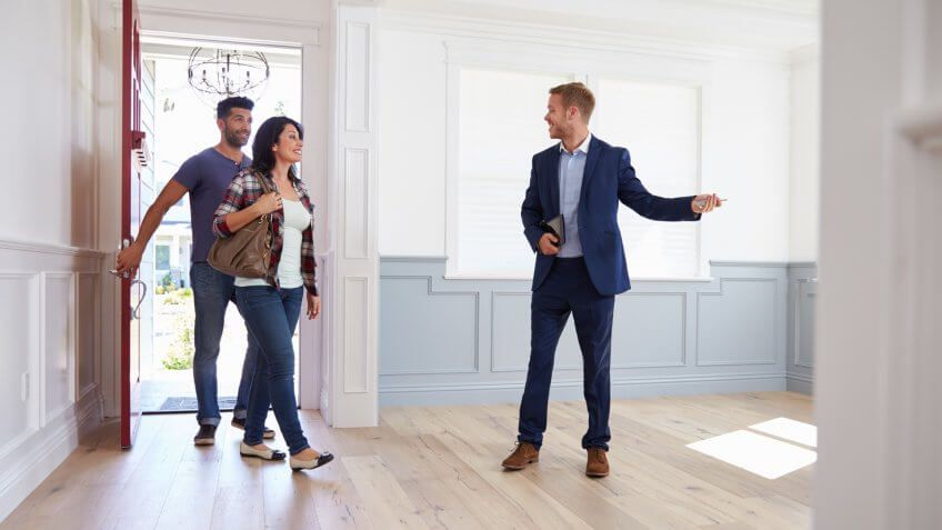Realtor Showing Hispanic Couple Around New Home.
