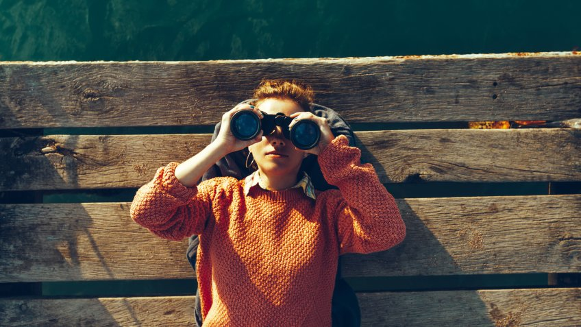 Young Girl Lies On A Pier Near The Sea And Looks Through Binoculars.