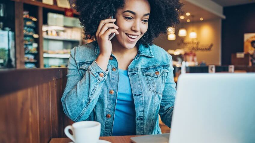 Smiling young African ethnicity woman using smart phone and laptop in cafe.