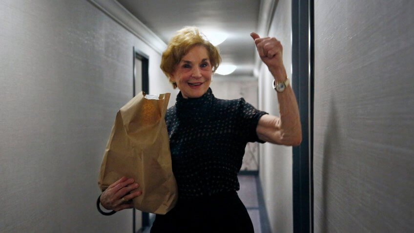 Carol Sterling, 83, gives a thumbs-up to Liam Elkind after he delivers groceries to her apartment as part of a newly formed volunteer group he cofounded, Invisible Hands.