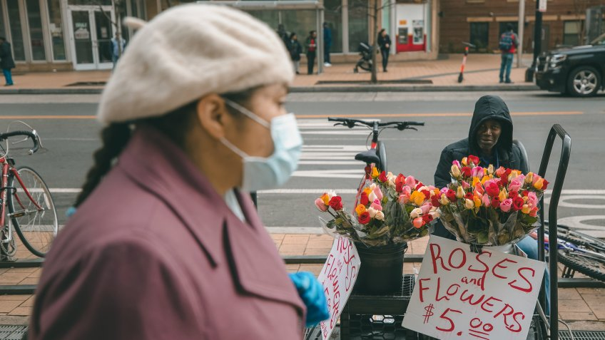 A street vendor sells flowers as a mask-wearing shopper walks in the Columbia Heights area in Washington, DC, USA, 19 March 2020.